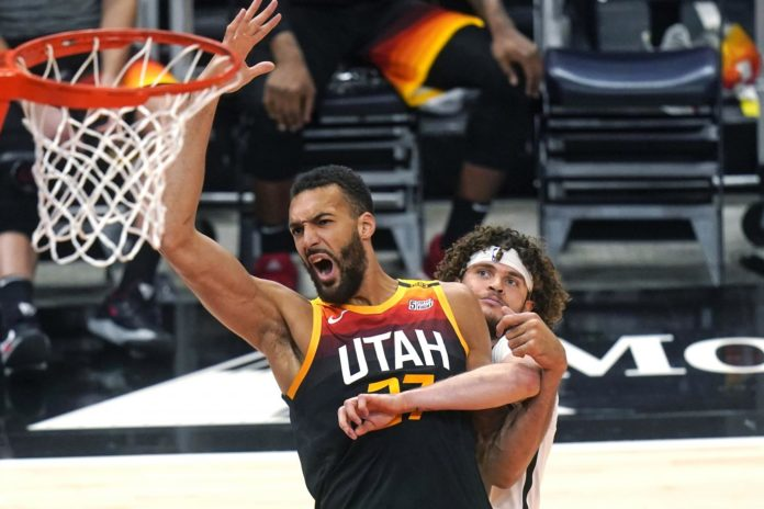 Utah Jazz center Rudy Gobert (27) and Brooklyn Nets guard Tyler Johnson, rear, work for position near the basket during the first half of an NBA basketball game Wednesday, March 24, 2021, in Salt Lake City. (AP Photo/Rick Bowmer)